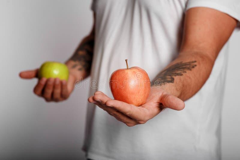 Жирный человек на белой предпосылке с яблоком в его руках человек выбрал здоровый образ жизни стоковая фотография rf