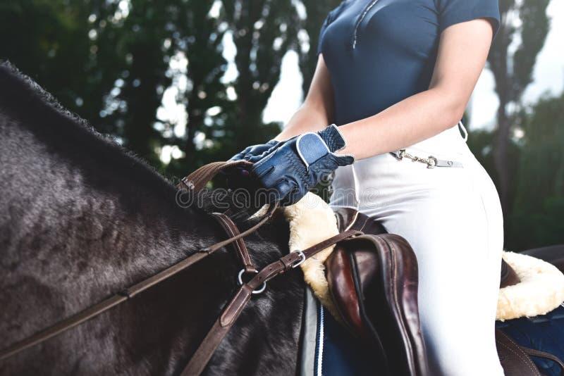 Жокей маленькой девочки тренирует лошадь к лошадиным скачкам на лете r стоковые изображения rf