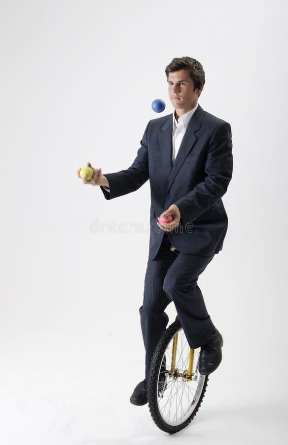 Жонглируя бизнесмен на unicycle стоковые фото