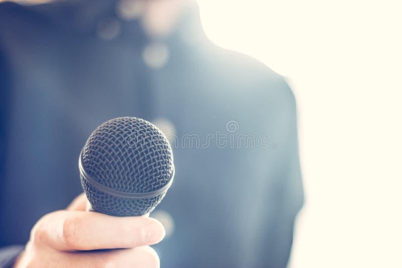 Журналист держит микрофон на переднем плане, расплывчатая предпосылка стоковые изображения
