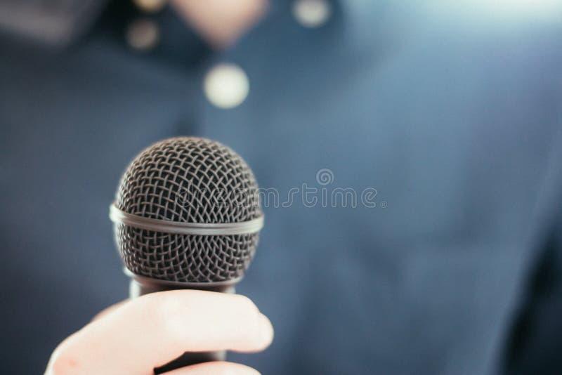 Журналист держит микрофон на переднем плане, расплывчатая предпосылка стоковая фотография