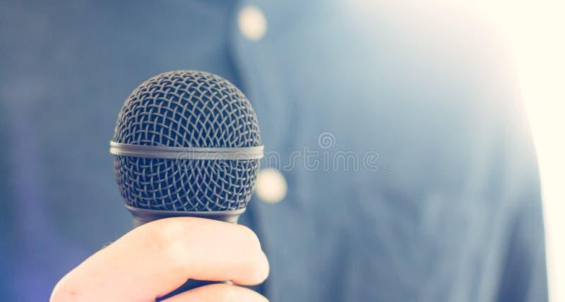 Журналист держит микрофон на переднем плане, расплывчатая предпосылка стоковое фото rf