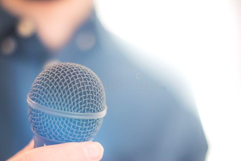 Журналист держит микрофон на переднем плане, расплывчатая предпосылка стоковая фотография rf