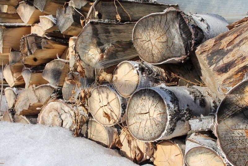 Журналы березовой древесины сложили в куче в снеге подготовленном для разжигать на зима в стоге стоковое фото