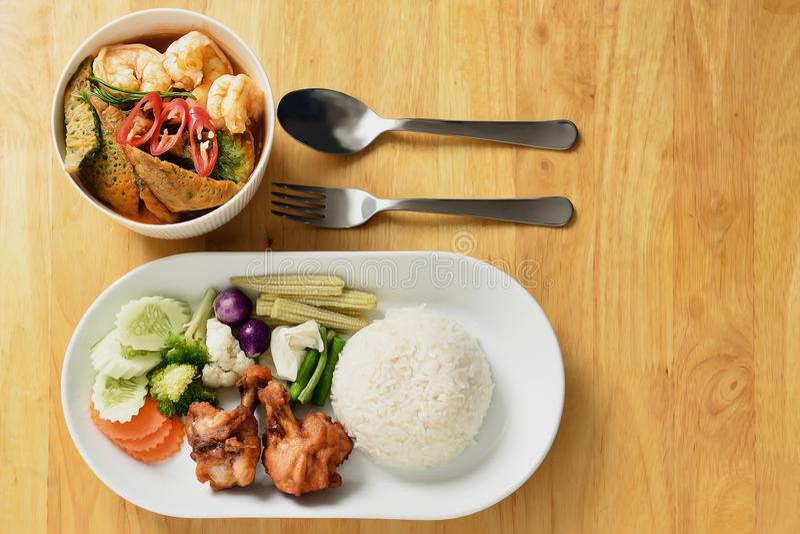 Жёлтое карри с акасийским овощным омлетом подается с жареными куриными палочками, рисом и разнообразием свежих овощей на стоковое изображение