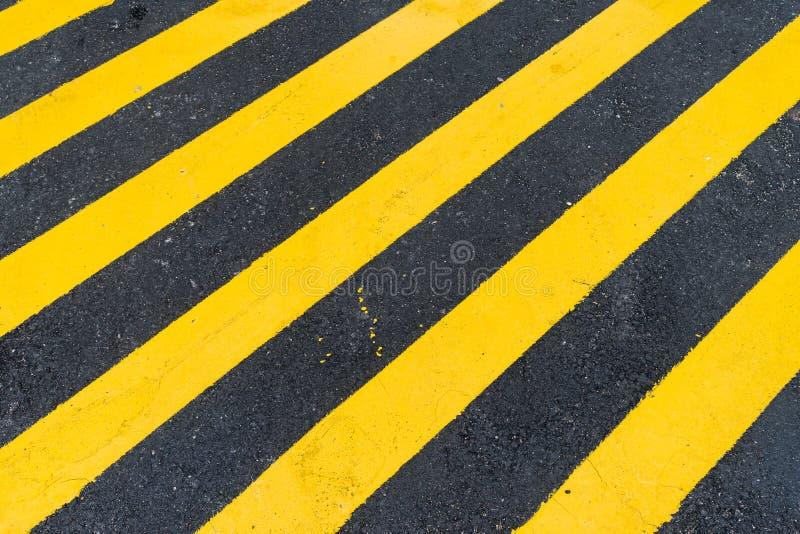 Заасфальтируйте предпосылку с раскосной черной и желтой предупреждающей нашивкой стоковое фото rf