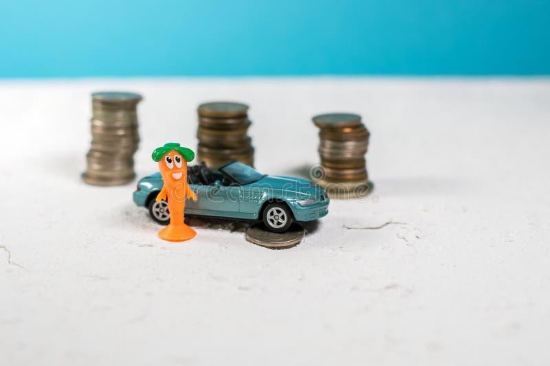 Забавляйтесь голубой cabriolet автомобиля на белой дороге затем усмехаться девушки игрушки под колесом автомобиля лежат деньги стоковое изображение rf