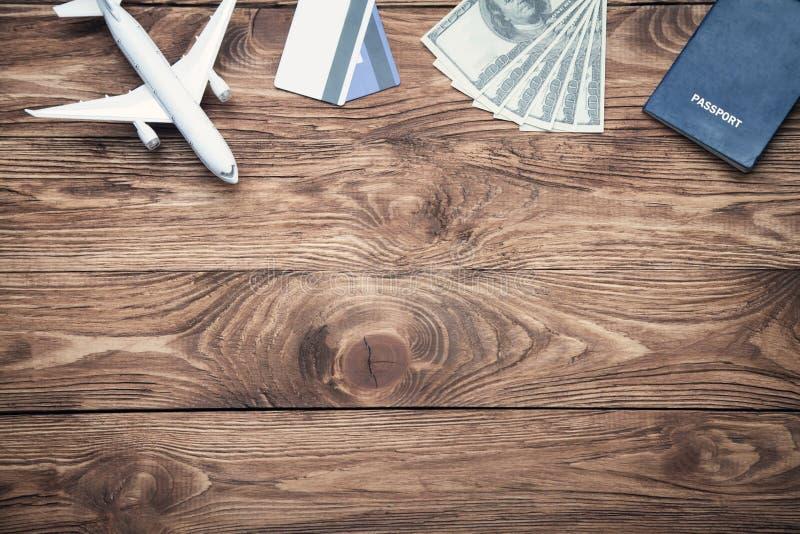Забавляйтесь самолет, кредитные карточки, доллары и пасспорт на деревянном des стоковые фотографии rf