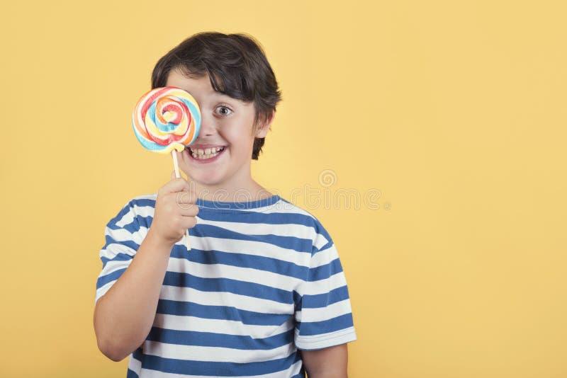 Забавный ребенок, покрывающий глаз с помощью леденца стоковое фото rf