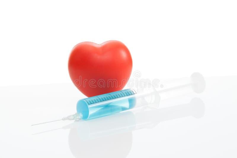 Забавляйтесь сердце и шприц с голубой внутренностью решения - съемкой студии стоковое фото rf