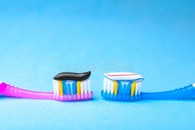 Забеливать зубную пасту обычные покрашен и черн от угля на зубной щетке Концепция Которая зубная паста, который нужно выбрать? стоковая фотография rf