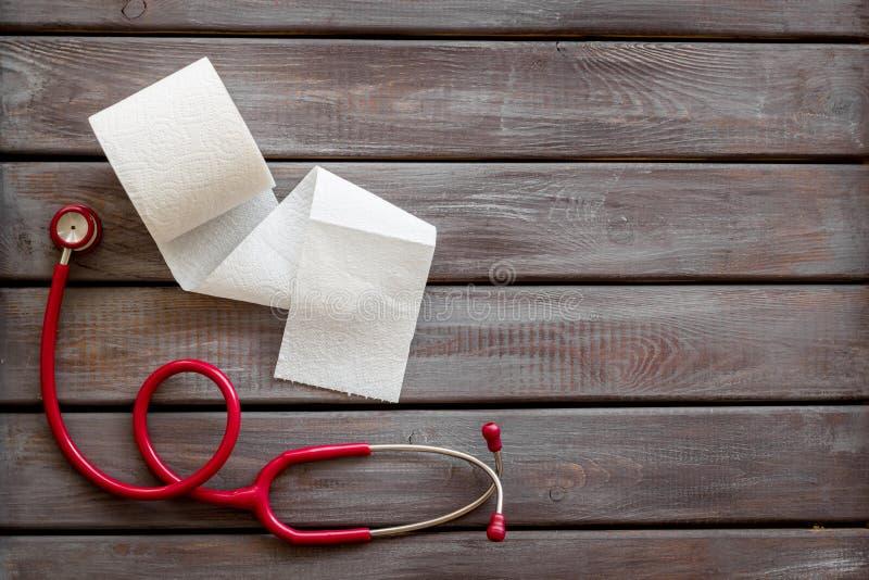 Заболевание концепции двоеточия с креном и стетоскопом туалетной бумаги на деревянном модель-макете взгляда сверху предпосылки стоковая фотография