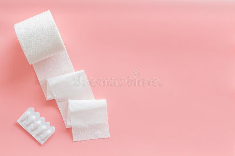 Заболевание концепции двоеточия с креном туалетной бумаги и ректальным суппозиторием на розовой насмешке взгляда сверху предпосыл стоковые фотографии rf