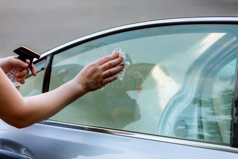 Забота автомобиля - женщина моя автомобиль вручную используя автомобиль чистки ткани microfiber стоковые фото