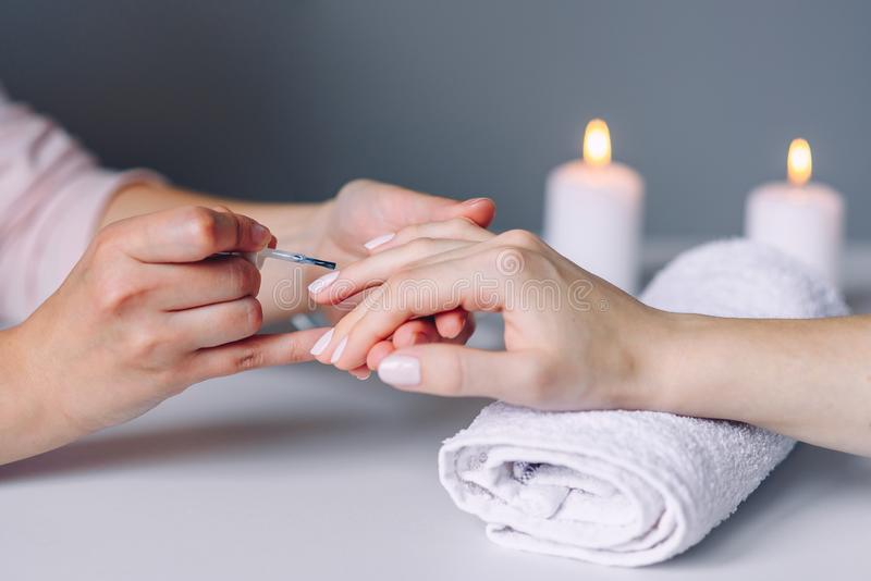 Забота и маникюр ногтя Ногти здоровой естественной женщины крупного плана в салоне красоты Рука Manicurist красит ногти клиента стоковые изображения