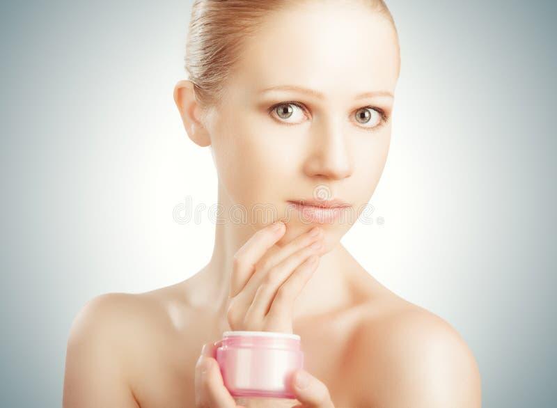 Забота кожи. девушка счастливой красоты здоровая с опарником сливк стоковое фото