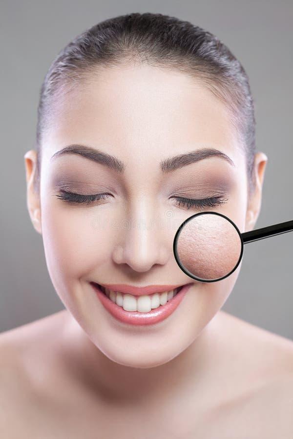 Забота кожи и концепция красоты - сторона красивой молодой женщины с улыбкой над серой предпосылкой дефект кожи на стороне loupe стоковое фото