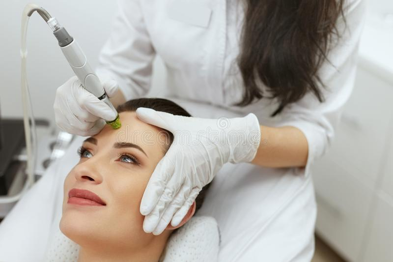 Забота кожи стороны Женщина получая лицевую гидро Exfoliating обработку стоковые фотографии rf