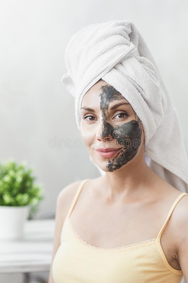 Забота кожи стороны Привлекательная молодая женщина в оболочке в полотенце ванны, прикладывая маску грязи глины для того чтобы см стоковые фотографии rf