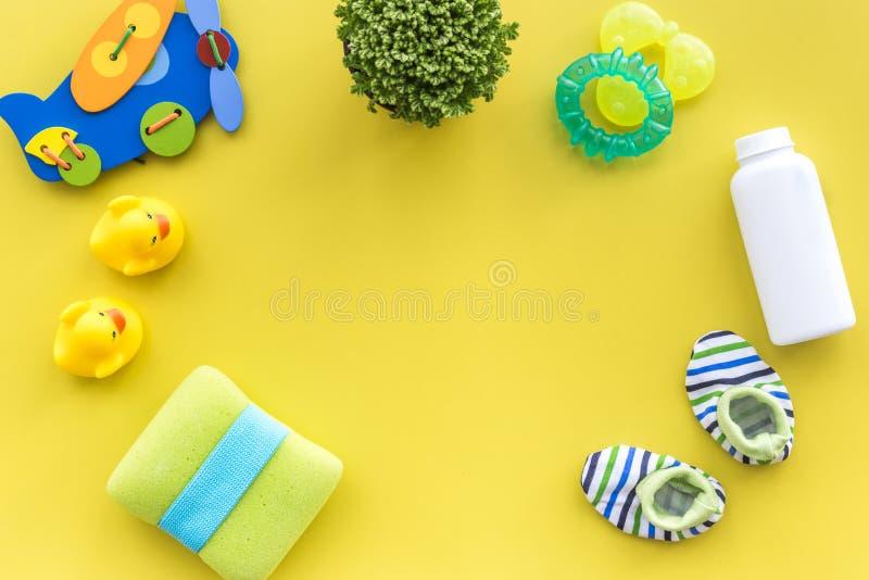 Забота младенца с комплектом, утятами и полотенцем ванны на желтом модель-макете взгляд сверху предпосылки стоковое фото
