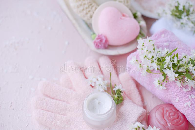 Забота руки курорта, соль моря, сливк и перчатки Цветки белы Розовая предпосылка установьте текст стоковое фото rf