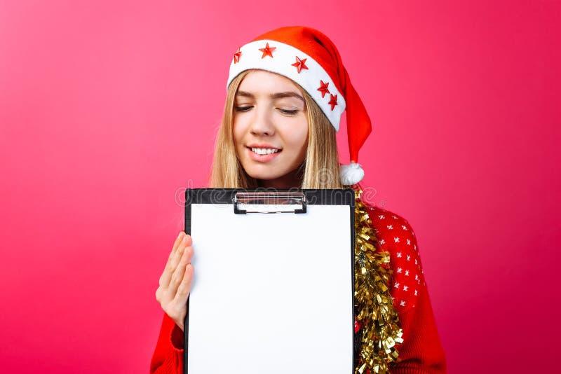 Заботливая девушка в красных свитере и шляпе Санты, держа таблетку стоковые фотографии rf