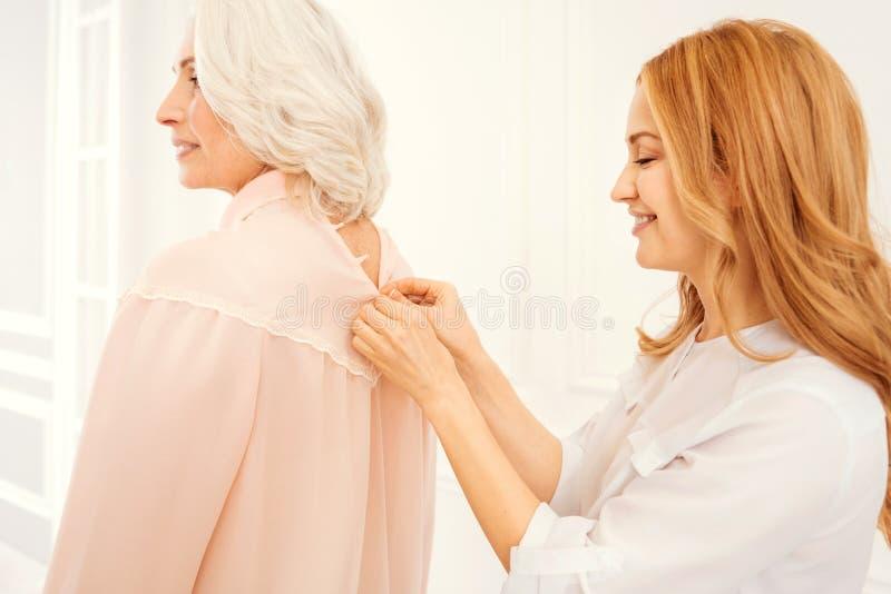 Заботливая зрелая дочь помогая ее старшей маме в одевать стоковая фотография