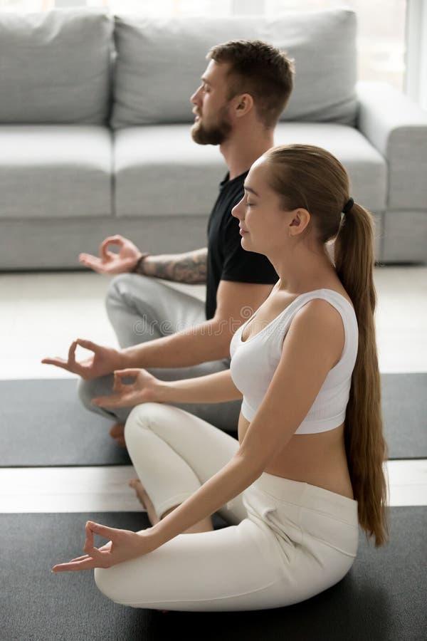 Заботливая йога человека и женщины практикуя на поле дома стоковые изображения rf