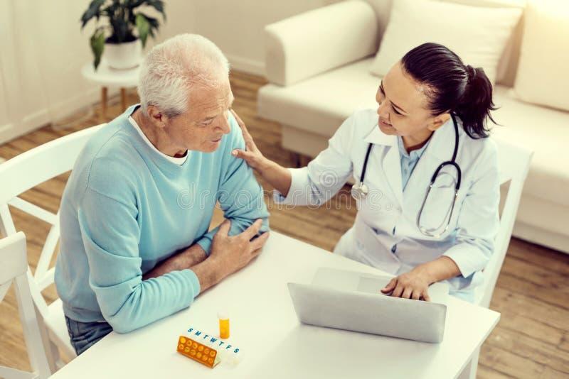 Заботливая медсестра веселя выбытый пациента и усмехаться стоковое изображение rf