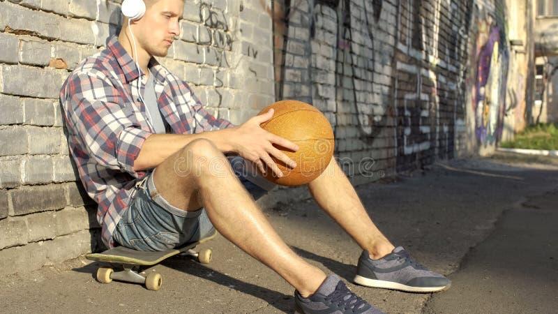 Заботливое мужское предназначенное для подростков усаживание на скейтборде и слушать к музыке в наушниках стоковые изображения rf