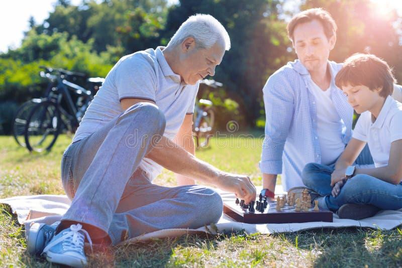 Заботливый дед играя шахмат с внуком стоковые изображения rf