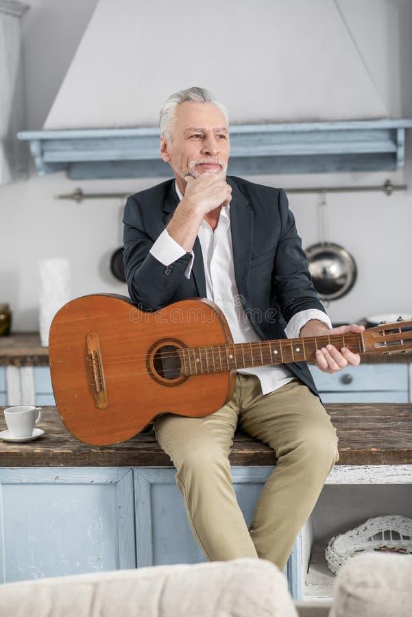 Заботливый зрелый человек держа гитару стоковая фотография