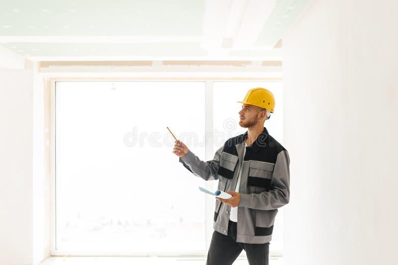 Заботливый инженер в рабочей одежде и желтом защитном шлеме держа p стоковые фотографии rf