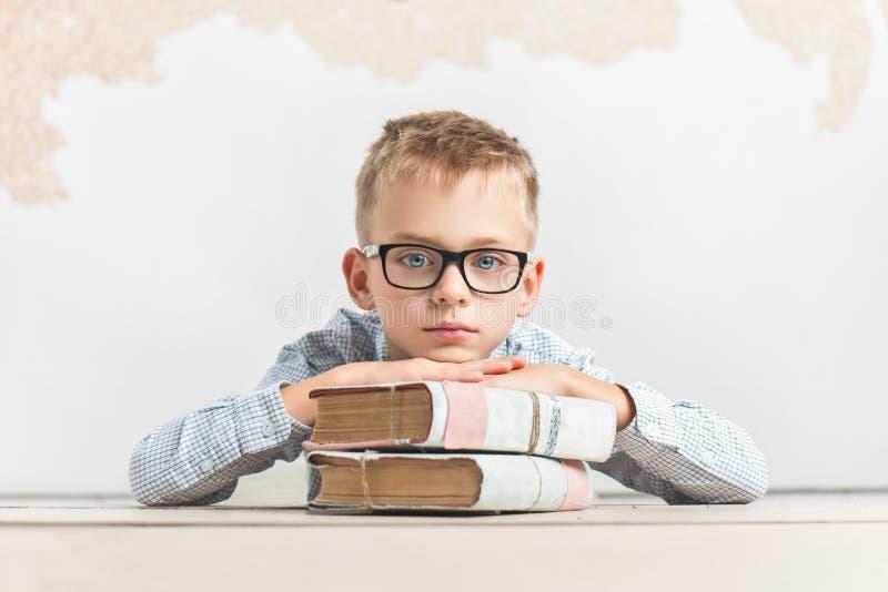 Заботливый школьник сидит на столе с книгами стоковое фото