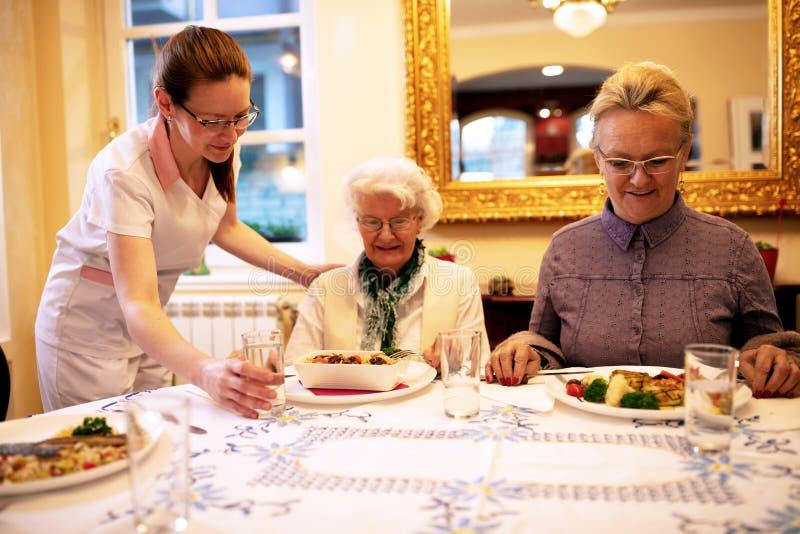 Заботя еды медсестры служа для обедающего стоковое изображение rf