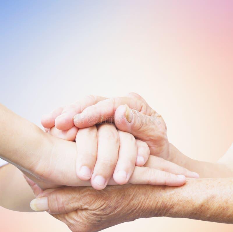 Заботя концепция: Руки ` s матери дня ` s матери морщинистые держат руки ` s ребенка плотно стоковая фотография rf