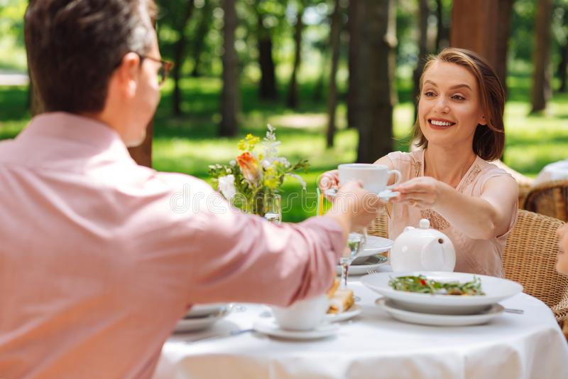Заботя любящая жена давая чашку чаю к супругу стоковое изображение