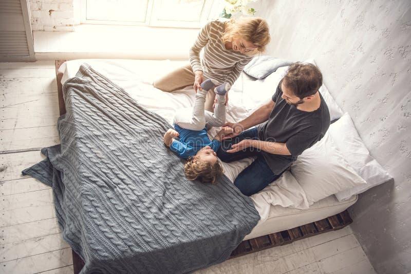 Заботя родители расслабляющие с сыном в уютной комнате стоковые фотографии rf
