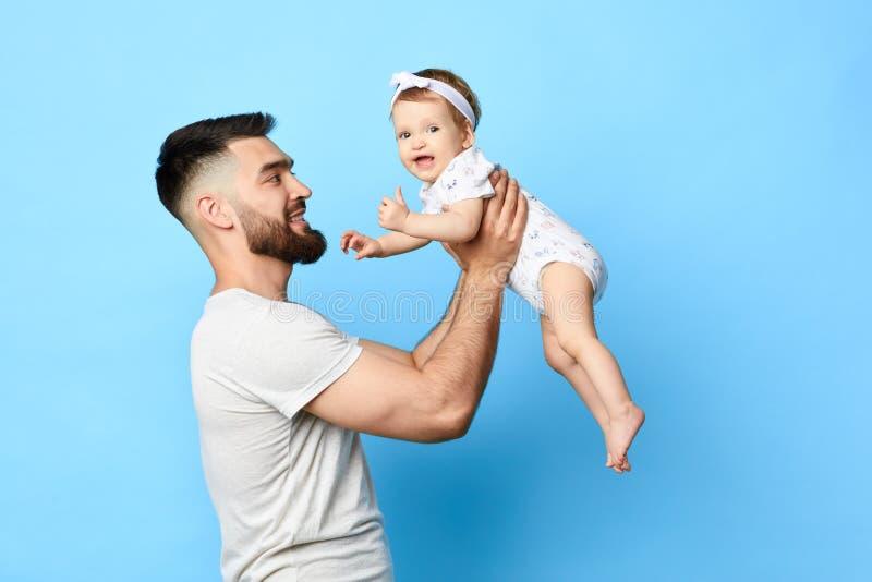 Заботя счастливый отец поднимая его дочь младенца вверх в воздухе стоковые изображения