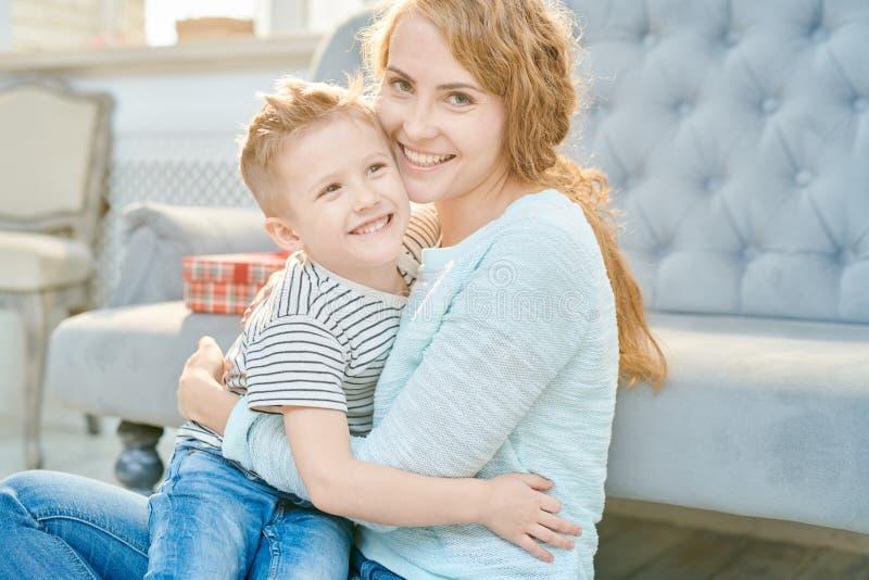 Заботя сын матери обнимая маленький стоковые изображения rf
