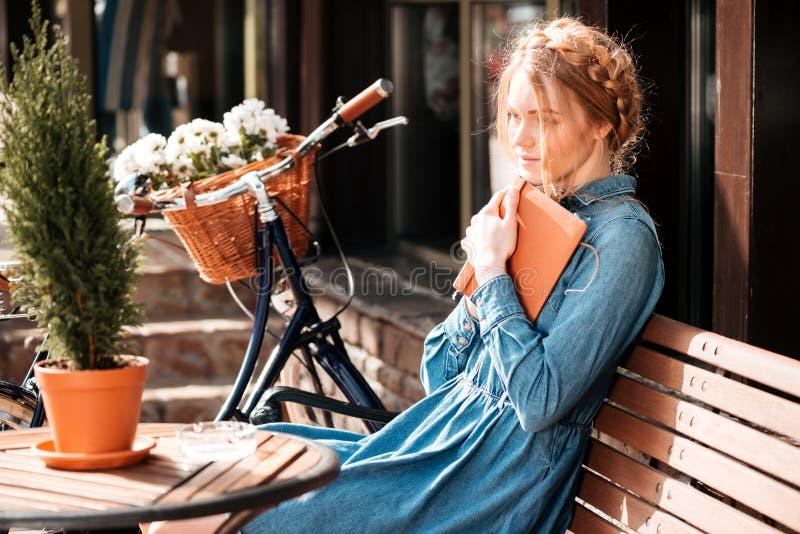 Заботливая книга readng женщины и мечтать на beanch outdoors стоковая фотография rf