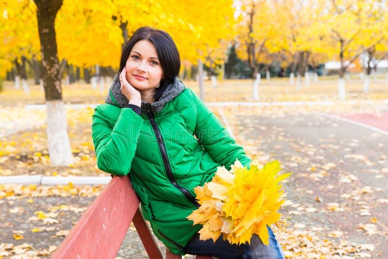 Заботливая молодая женщина ослабляя на стенде осени стоковые фото