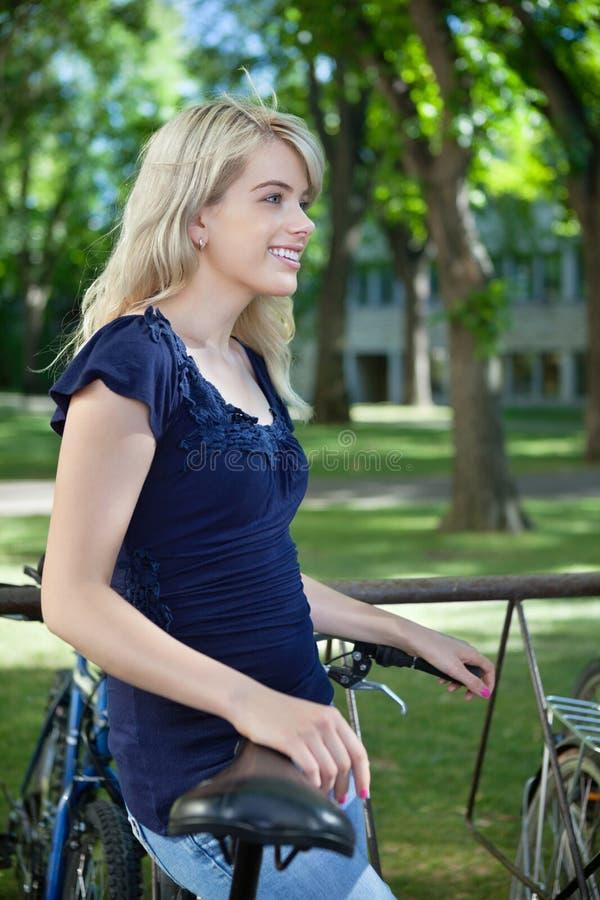 Заботливая студентка стоя с ее велосипедом стоковая фотография rf