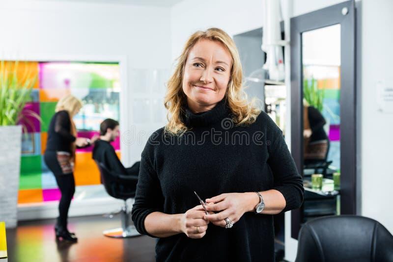 Заботливое женское удерживание парикмахера Scissor стоковые фотографии rf