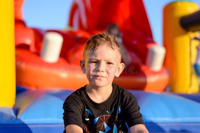 Заботливый мальчик в спортивной площадке детей стоковое изображение