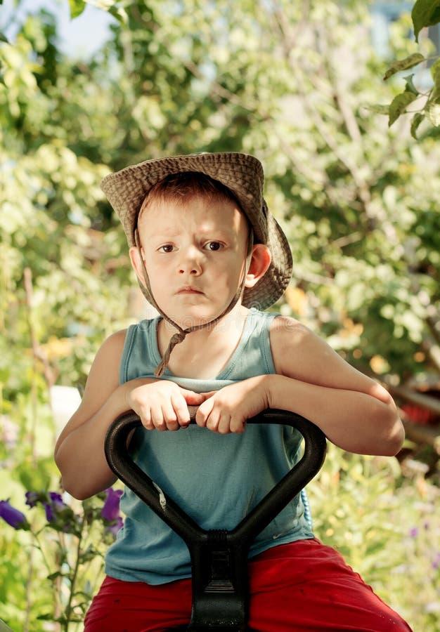Заботливый молодой мальчик сидя в саде страны стоковое изображение rf