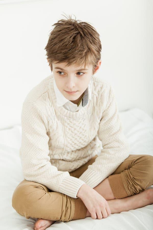 Заботливый молодой мальчик сидя на его кровати стоковые фото