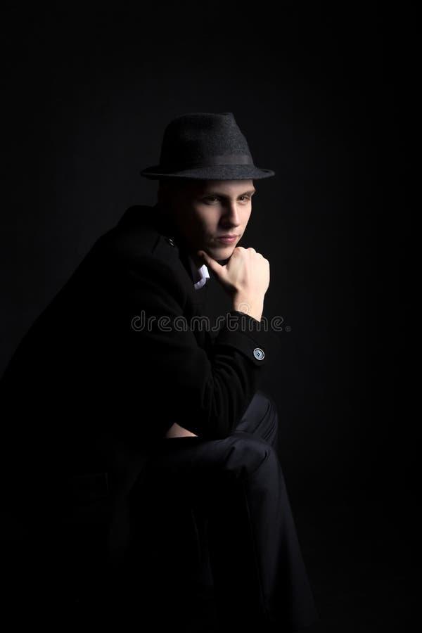 Заботливый молодой человек в шляпе в темноте стоковая фотография rf