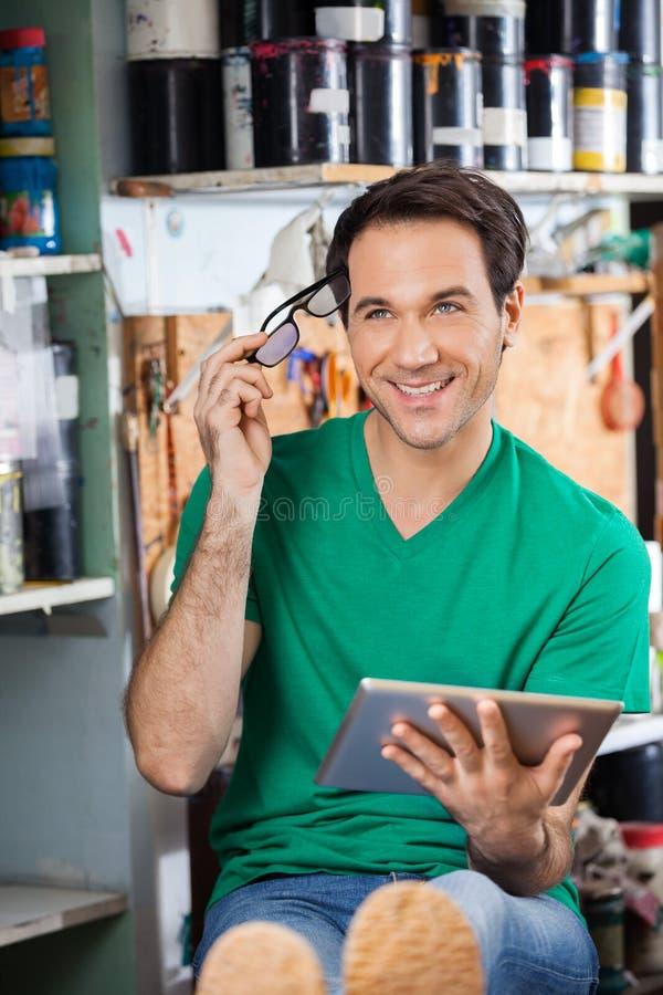 Заботливый работник держа Eyeglasses и планшет на самом деле стоковая фотография