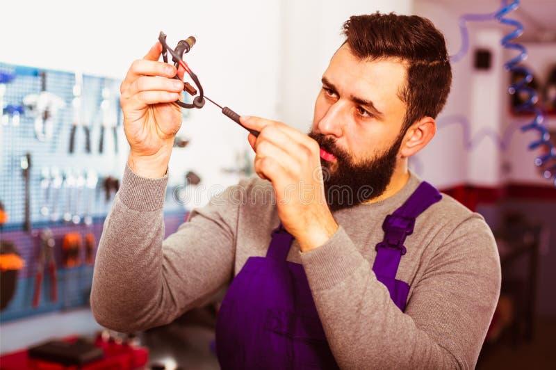 Заботливый работник человека работая на восстанавливать мотоцилк в мастерской стоковые фото
